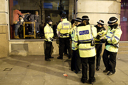 """© licensed to London News Pictures. Manchester, UK 17/12/2011. Despite freezing temperatures, """"Mad Friday"""" revellers in Manchester enjoy what is traditionally the busiest night of the year for emergency services, before Christmas. Police detain a man outside a nightclub as those inside look on. Please see special instructions for usage rates. Photo credit should read Joel Goodman/LNP"""