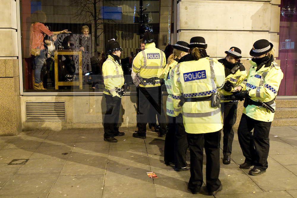 "© licensed to London News Pictures. Manchester, UK 17/12/2011. Despite freezing temperatures, ""Mad Friday"" revellers in Manchester enjoy what is traditionally the busiest night of the year for emergency services, before Christmas. Police detain a man outside a nightclub as those inside look on. Please see special instructions for usage rates. Photo credit should read Joel Goodman/LNP"