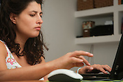 woman in her 30s works from home on her laptop computer - Model release available