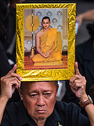 29 OCTOBER 2016 - BANGKOK, THAILAND:  A man holds a picture of the Bhumibol Adulyadej, the King of Thailand, while he waits to go into the Grand Palace to homage to the King. Saturday was the first day Thais could pay homage to the funeral urn of the late Bhumibol Adulyadej, King of Thailand, at Dusit Maha Prasart Throne Hall in the Grand Palace. The Palace said 10,000 people per day would be issued free tickerts to enter the Throne Hall but by late Saturday morning more than 100,000 people were in line and the palace scrapped plans to require mourners to get the free tickets. Traditionally, Thai Kings lay in state in their urns, but King Bhumibol Adulyadej is breaking with tradition. His urn reportedly contains some of his hair, but the King is in a coffin,  not in the urn. The laying in state will continue until at least January 2017 but may be extended.      PHOTO BY JACK KURTZ
