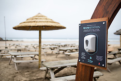 © Licensed to London News Pictures. 04/07/2020. Perranporth, UK. A hand sanitising station is seen outside the Watering Hole, (the UK's only bar on the beach) as it opens for the first time since the COVID-19 lockdown began. Today marks a lift in COVID-19 restrictions, as pubs are allowed to open, whilst customers must still follow social distancing guidelines. Tens of thousands of tourists are due to arrive in Cornwall over this weekend, as overnight stays within England are also allowed. Photo credit : Tom Nicholson/LNP