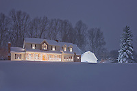 Snow covered house in the winter at Christmas during twilight in snow storm