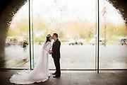 bride and groom kissing in archway window with water flowing down the glass