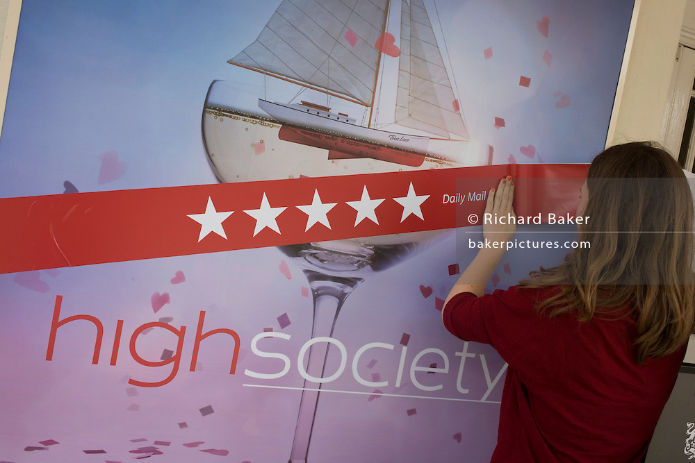 Theatre employees from the Old Vic stick up a 5-star rating banner for their newest play, High Society in Waterloo, south London.