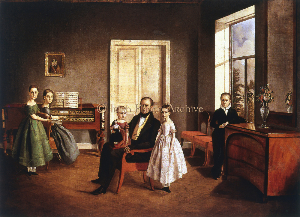 Portrait of a family in an interior. Father central with two youngest children. Mother? at square piano with daughter beside her. Son stands apart. Anonymous, c1840. Oil on canvas.  Russian Museum, St Petersburg.