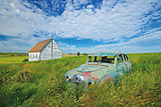 Old Austin car and church in field in ghost town <br /> Neidpath<br /> Saskatchewan<br /> Canada