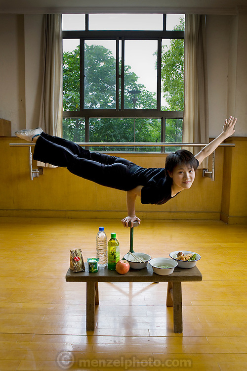 Cao Xiaoli, a professional acrobat, balances on one hand with her day's worth of food at Shanghai Circus World in Shanghai, China.  (From the book What I Eat: Around the World in 80 Diets.) The caloric value of her day's worth of food on a typical day in June was 1700 kcals.  She is 16 years of age; 5 feet, 2 inches tall; and 99 pounds. Cao Xiaoli lives in  a room with nine other girls. She started her career as a child, performing with a regional troupe in her home province of Anhui. Now she practices five hours a day, attends school with the other members of her troupe, and performs seven days a week. She says what she likes best about being an acrobat is the crowd's reaction when she does something seemingly dangerous. MODEL RELEASED.