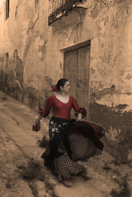 A Spanish woman walking along a traditional Spanish street wearing a Flamenco style dress