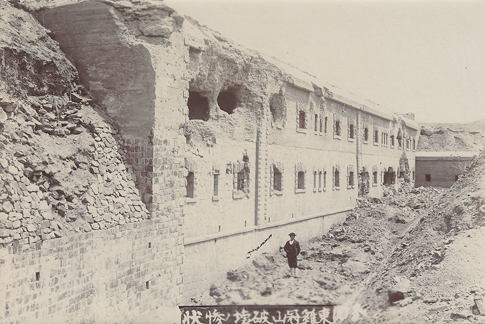 Photographer Mitsumura Toshimo amid the battlefront ruins, Liaoning Province, China. Russo-Japan War 1905.<br />