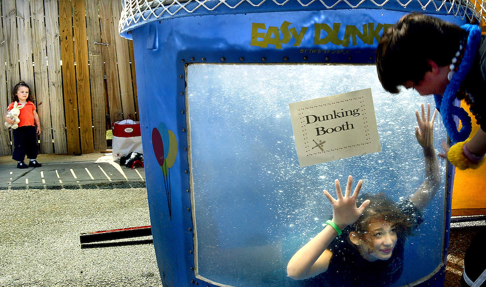 "Sean Brookhart, age 12, right, from Jacksonville, storms up to Emily Scheinberg, age 14, from Jarrettsville, to make a face at her while submerged in the dunking booth. All the while, Maggie Possidente, age 2, left, from Cockeysville, finds some shade and takes in the festivities with her stuffed rabbit during ""Ben's Big League Bash,"" a carnival fundraiser missioned to raise money for a baseball field memorializing four-year-old Ben Huxtable, who died from heart failure after a baseball hit him in the chest during his father's rec. council game last Father's Day. The carnival, which was held at Chestnut Grove Presbyterian Church in Jacksonville Saturday, September 10, 2005, was thought up by the church's Senior and Middle School Youth Groups, of which Emily is a member. Ben also went to pre-school at the Jacksonville church. (Staff Photo by Matt Roth)."