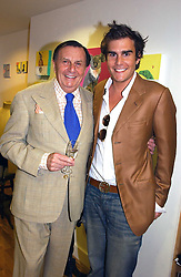 Left to right, BARRY HUMPHRIES and OSCAR HUMPHRIES  at an exhibition of art by Oscar Humphries entitles 'Post-Nuclear Family' held at Nutters, Lower Ground, 12 Savile Row, London on 8th June 2006.<br />
