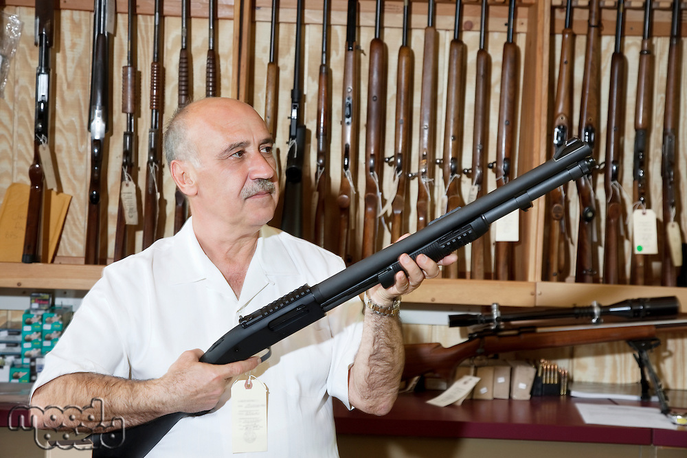 Mature gun store owner looking at weapon in shop