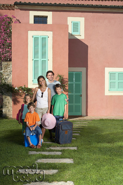 Portrait of family with three children (6-11) with luggage in front of house