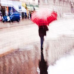 Intentionally motion blurred abstract image of a woman walking with a red umbrella under the rain
