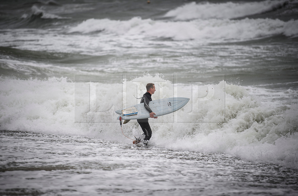 © Licensed to London News Pictures. 18/09/2018. Brighton, UK. A surfer braves rough sea waters during wet and windy conditions on the sea front at Brighton. The recent warm spell is set to change for many over the next few days in the south. Photo credit: Ben Cawthra/LNP