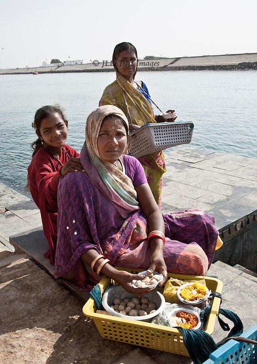 three Gujarati women selling fish food at Dwarka.