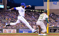 April 13, 2017 - Kansas City, MO, USA - The Kansas City Royals' Lorenzo Cain beats the throw to Oakland Athletics first baseman Ryon Healy (25) in the third inning for a single at Kauffman Stadium in Kansas City, Mo., on Thursday, April 13, 2017. (Credit Image: © John Sleezer/TNS via ZUMA Wire)