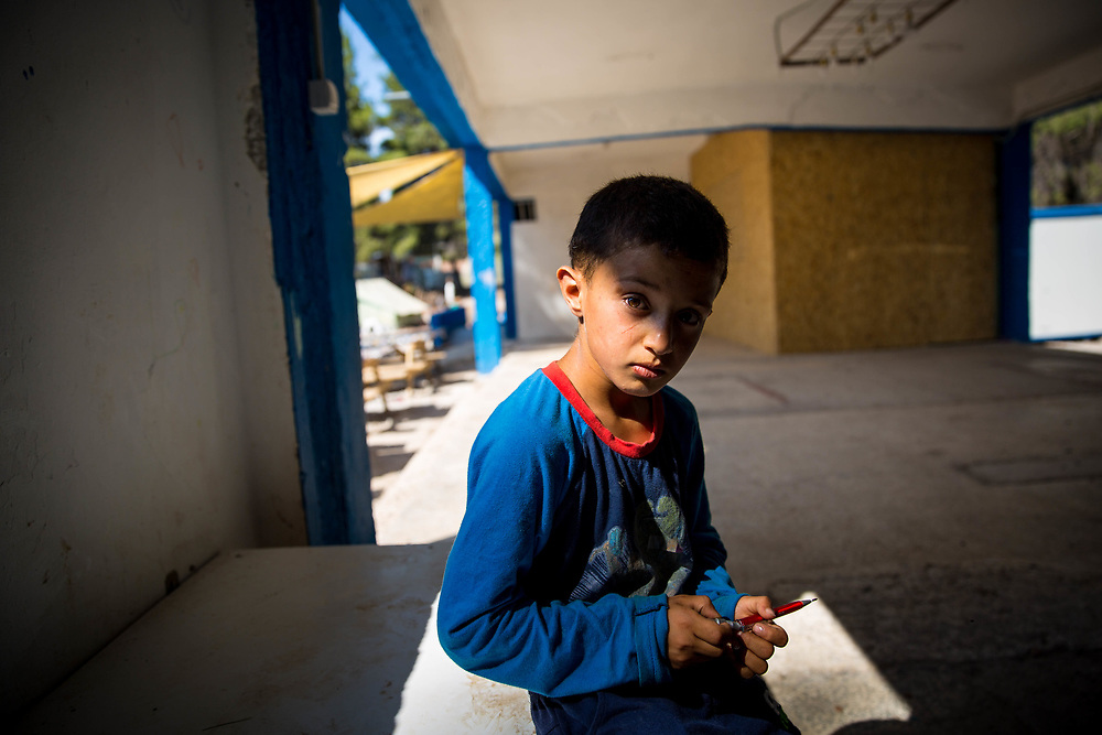 Salah, 8, from Syria, shows signs of depression, living in a makeshift camp in Greece, after fleeing the Syrian War with his family. Ritsona Refugee Camp, Greece, July 2016.