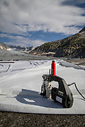 Climate | Albedo | Rhone: A hand held sewing machine used to stitch together huge fleece blankets to prevent the popular ice tunnel at the mouth of the Rhone Glacier from melting. After a winter with record amounts of snow, most of it was gone when this image was taken on July 14th 2018, exposing the darker ice. While snow is a brilliant reflector of the energy from the sun, the darker ice absorbs the energy instead, accelerating the melting of the glacier. The color and darkness of glacier ice vary all over the world, depending on build-up of pollution, age of the ice, particles picked up by the ice and by microorganisms in the ice. The glacier ice is however rarely white as snow. With shorter winters and vanishing snow cover, the melting of the glaciers is accelerating.<br /> <br /> The Rhone Glacier (pictured) now melts more than 70 centimeters in thickness every week in the summer months. Between 1996 and 2006, an estimated 0.9 billion cubic metres of water melted yearly from the Swiss glaciers. That number is likely much higher today. Switzerland just had the hottest July since 1864, it has the lowest rainfall since 1921, and the rivers are running at record low levels. The covering of the glacier is the idea of Philipp Carlen, who owns and operates an ice cave at the mouth of the glacier. The glacier is still melting, but by covering it with blankets, he is able to attract tourists who are coming to see the dying glacier.