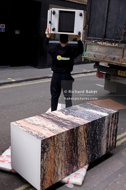Clearance workmen remove shop fittings in a Soho sidestreet.