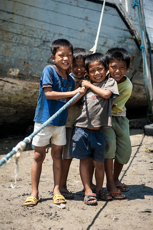 Portrait of boys playing near a boat on a beach in South Sulawesi, Indonesia