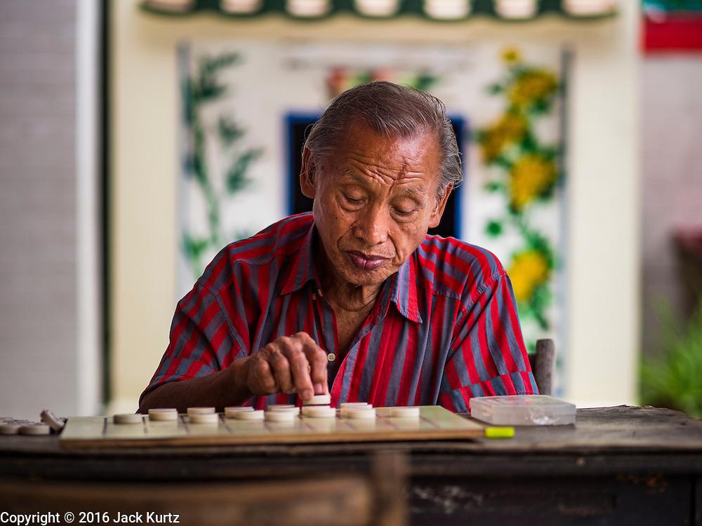 30 JUNE 2016 - BANGKOK, THAILAND: A man plays Chinese checkers by himself at a Chinese shrine in Bangkok.        PHOTO BY JACK KURTZ