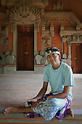 Young Balinese man sits down for a break at Goa Gajah temple to relax and check his cell phone messages.