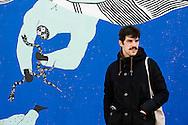 Street art in Dugave, Zagreb, Croatia. Croatian street artist Sretan Bor in front of one of his murals.