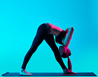 one caucasian woman exercising yoga exercices  in silhouette studio isolated on blue background
