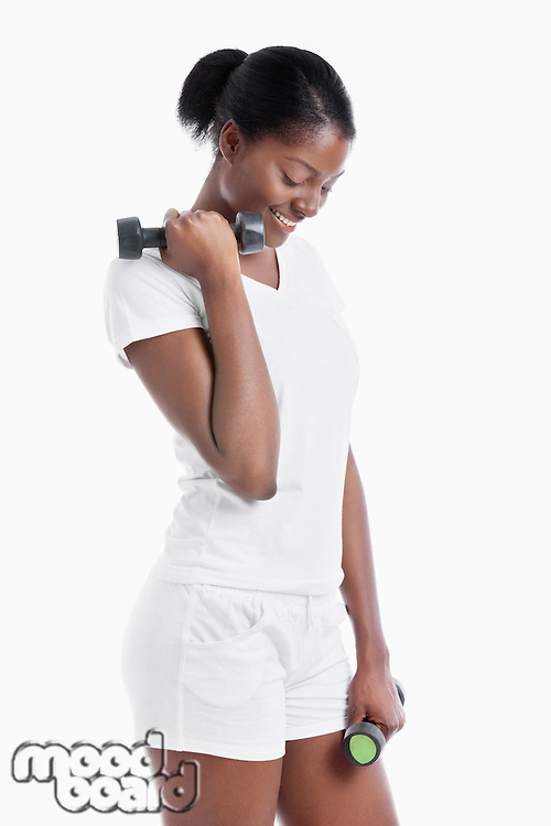 Thoughtful African American young woman with dumbbells standing over white background