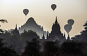 Hot air balloons rise like exclamation marks above the buddhist pagodas on the Irawaddy at Bagan (Pagan).