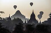 Hot air balloons rise like exclamation marks above the buddhist pagodas on the Irawaddy at Bagan (Pagan).
