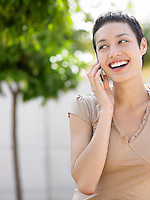 Smiling young woman on cell phone in plaza courtyard