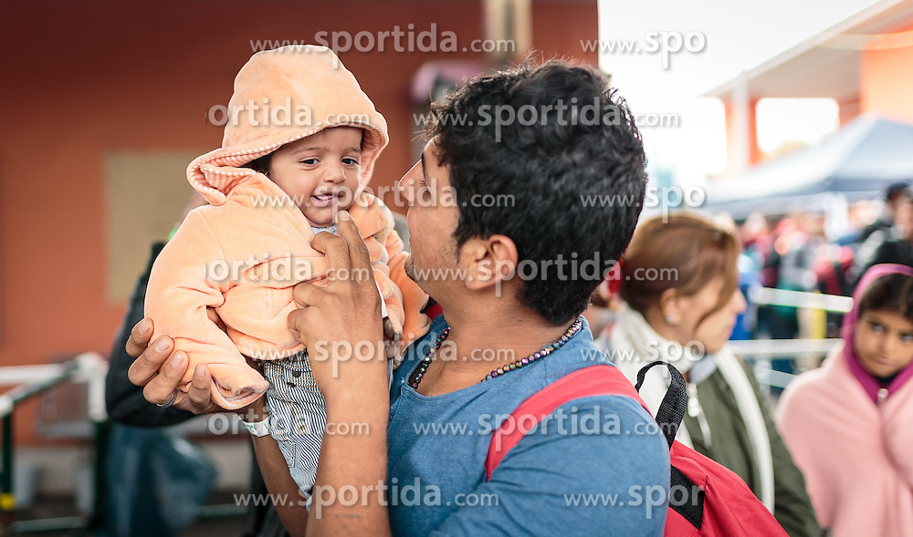 14.10.2015, Bahnhof, Freilassing, GER, Flüchtlingskrise in der EU, im Bild Flüchtlinge warten auf ihren Sonderzug, ein Vater spielt mit seinem Kleinkind // Refugees wait for their special train, a father playing with his toddler, Railway Station, Freilassing, Germany on 2015/10/14. EXPA Pictures © 2015, PhotoCredit: EXPA/ JFK