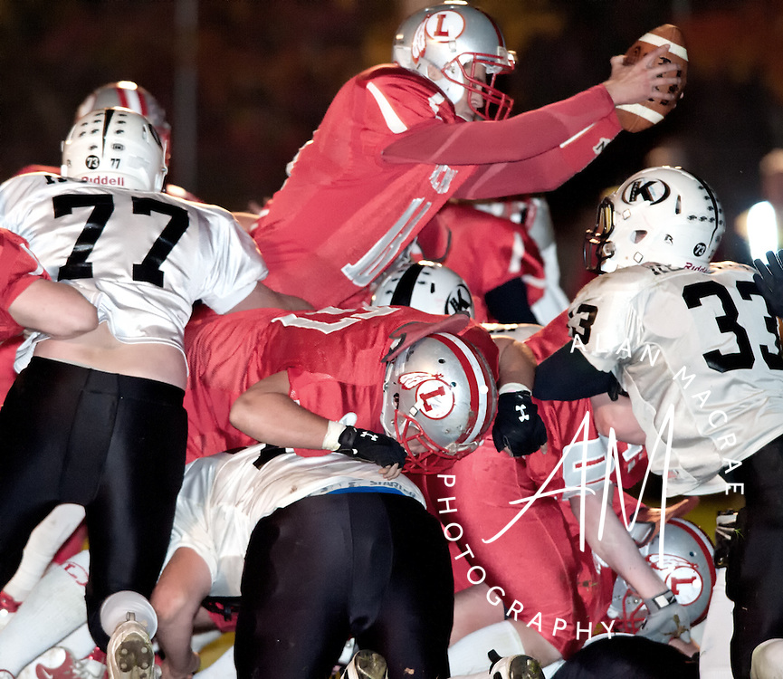 Laconia quarterback Hunter Briggeman leaps over the pile to gain inches, and a touchdown, in Friday's game against Kennett at Laconia High School.  (Alan MacRae/for the Laconia Daily Sun)