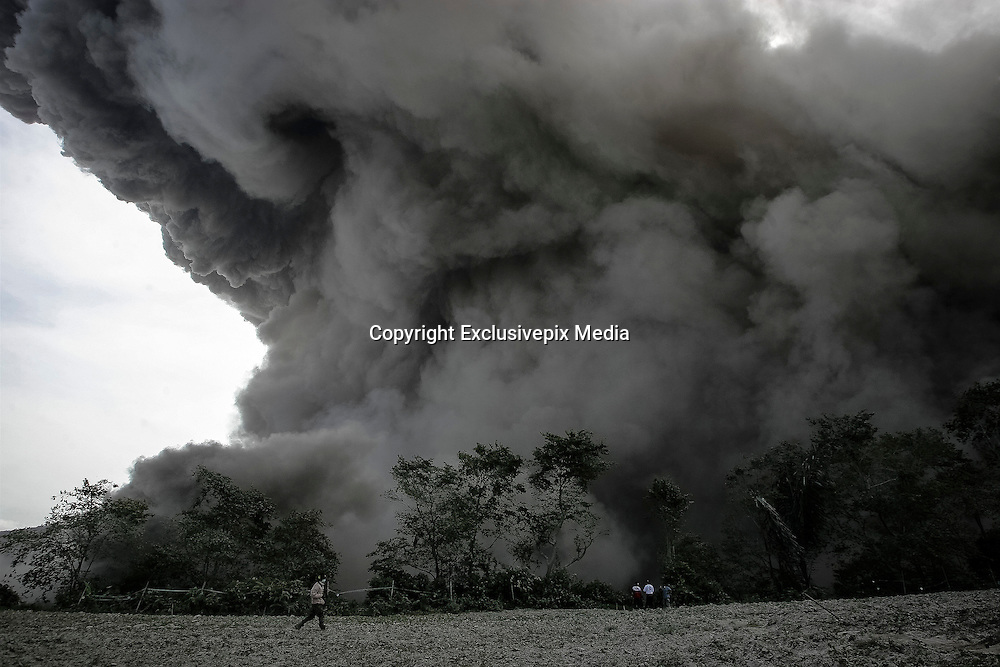 KARO, NORTH SUMATRA, INDONESIA-JUNE 28:<br /> <br /> Resident's look on as volcanic ash spread from mount sinabung seen at Karo, North Sumatra, Indonesia. June, 28. 2015. Over 10.000 Residents living near the Mount Sinabung volcano on Indonesia's Sumatra island were told to evacuate following a sharp increase in volcanic activity.<br /> &copy;Nira Cahaya/Exclusivepix Media