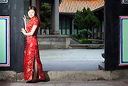 A Chinese / Taiwanese woman in a tradition qipao dress welcomes you to the Taipei Confucius Temple.