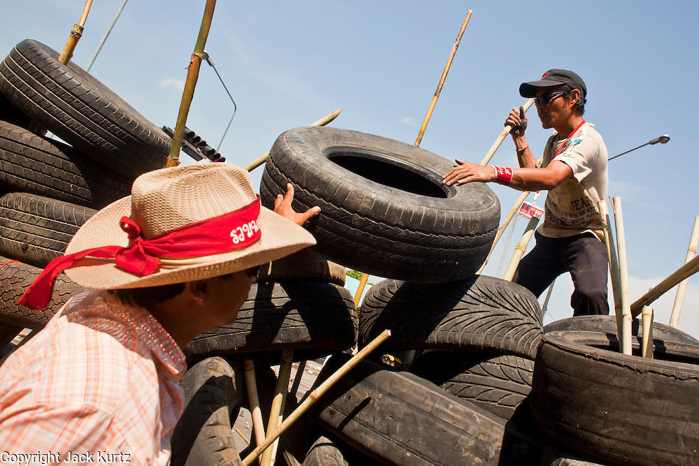 Apr. 30 - BANGKOK, THAILAND: Red Shirts rebuild a barricade in Sala Daeng after they tore it down. The Red Shirts moved one of their barricades in the Sala Daeng Intersection in Bangkok Friday In one of the first positive moves to take place since the Red Shirts occupied central Bangkok in early April. The barricade was moved far enough back to open one lane of traffic on  Ratchadamri Street to allow ambulance access to King Chulalongkorn Memorial Hospital, a large hospital at the intersection. Many of the patients in the hospital have been moved to other hospitals because a group of Red Shirts entered the hospital Thursday looking for Thai security personnel, who were not in the hospital. The stand off between the Red Shirts and the government enters its third month in May. The Red Shirts continue to call for Thai Prime Minister Abhisit Vejjajiva to step down and dissolve parliament and demand the return of ousted Prime Minister Thaksin Shinawatra.   PHOTO BY JACK KURTZ