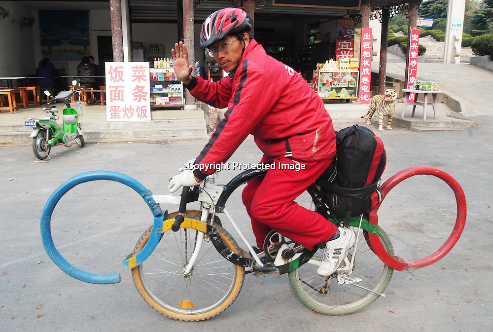 Dec 9, 2007, Yangzhou, Meng Jie, a Yinchuan resident ride on his converted bicycle in the form of the Olympic rings. Meng plans to ride the bike around the country after it took him two months to create this bicycle.