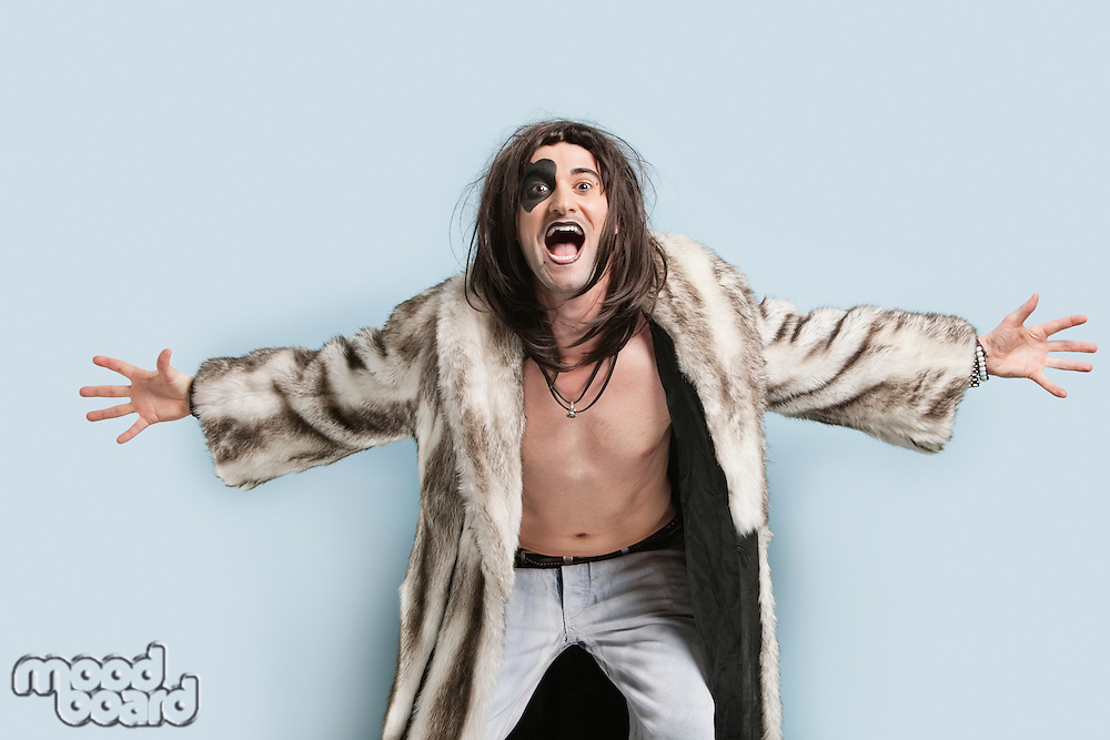 Portrait of young man in fur coat screaming against light blue background