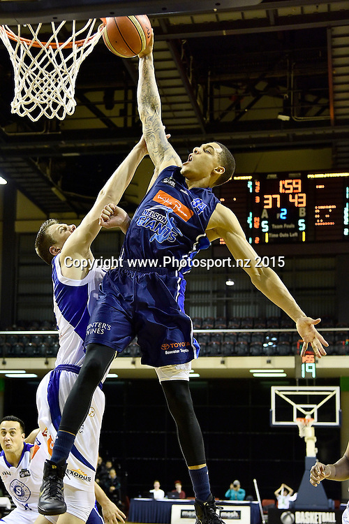 McKenzie Moore of the Giants slam dunks the ball with Hugh Quinlvan of the Saints during the NBL semi final basketball match between Wellington Saints and Nelson at the TSB Arena in Wellington on Saturday the 4th of July 2015. Copyright photo by Marty Melville / www.Photosport.nz