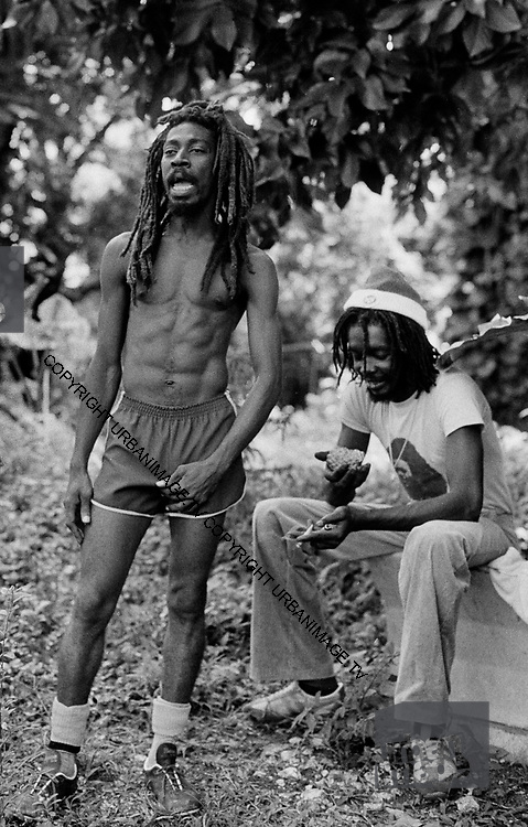 Peter Tosh shares a spliff with Bunny Wailer on his Farm in Hectors River Portland Jamaica. 1978