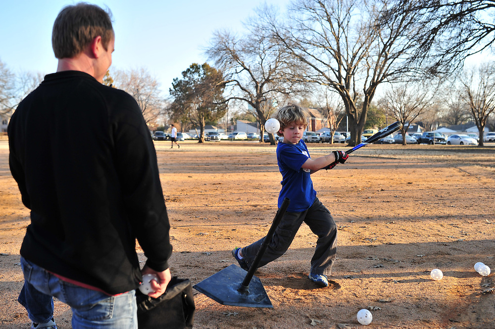 Carson Cason, 6, enjoys the warm weather with his father Chris Cason as they practice baseball at Burleson Park near SMU on Wednesday, January 20, 2013 in Dallas, Tx. (Cooper Neill/The Dallas Morning News)
