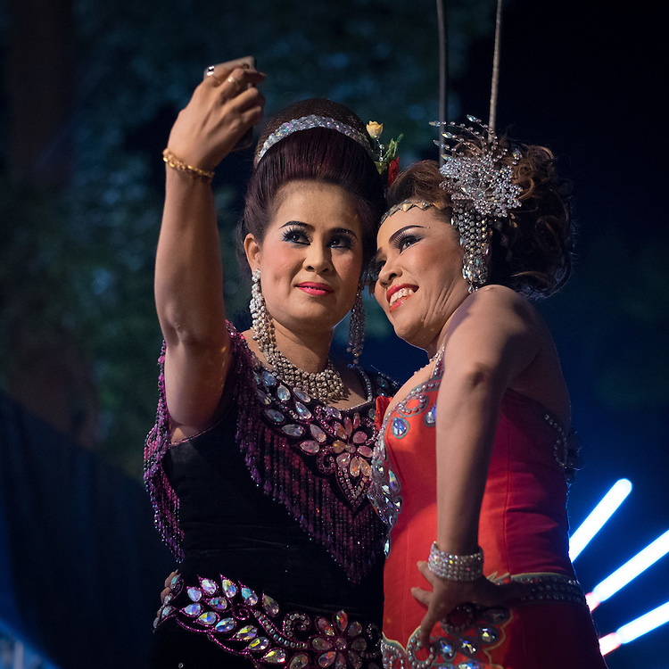 Performers take a selfie backstage at a Thai folk theatre performance, in Nakhon Nayok, Thailand, March 19, 2015