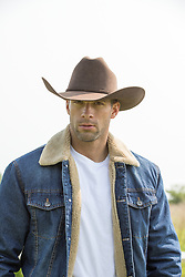 portrait of a hot cowboy in a denim jacket