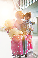Portrait of mother reuniting and kissing her daughter on forehead in airport
