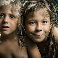 Female children with blonde hair with palm trees in background