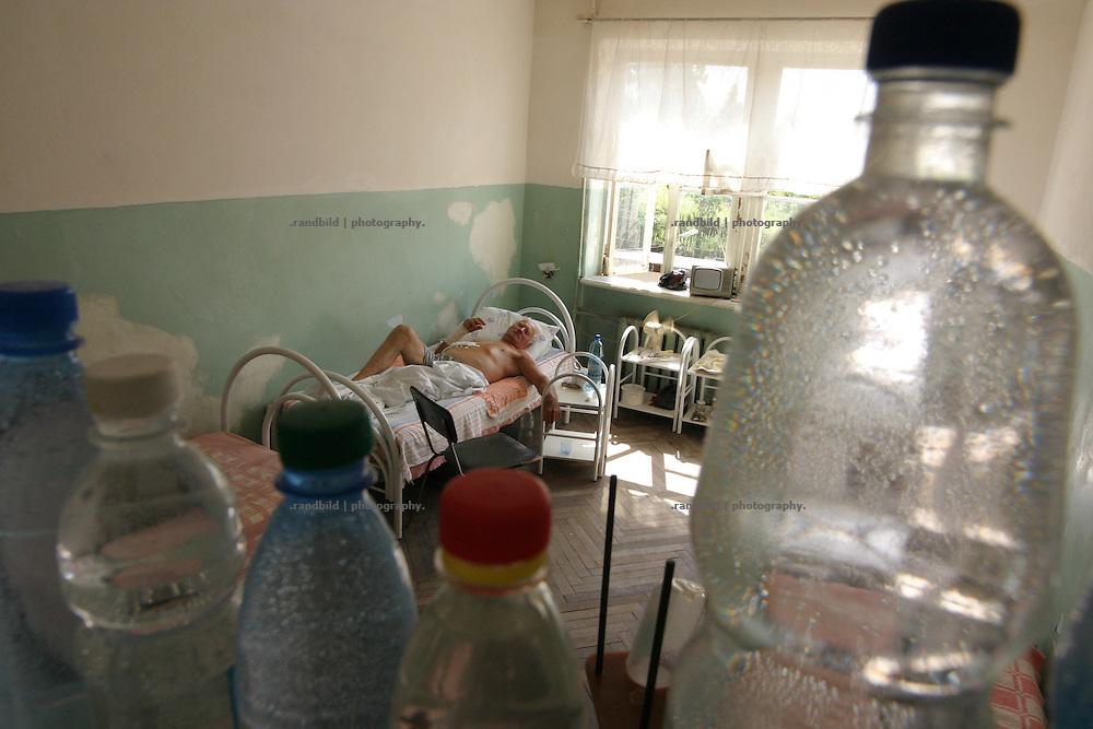 Georgien/Abchasien, Suchumi, 2006-08-27, Krankenzimmer mit gerade operierten Patienten im Republik-Krankenhaus von Suchumi. Wegen der unsicheren  Wasserversorgung wird Trinkwasser in Flaschen gesammelt. Abchasien erklärte sich 1992 unabhängig von Georgien. Nach einem einjährigen blutigen Krieg zwischen den Abchasen und Georgiern besteht seit 1994 ein brüchiger Waffenstillstand, der von einer UNO-Beobachtermission unter personeller Beteiligung Deutschlands überwacht wird. Trotzdem gibt es, vor allem im Kodorital immer wieder bewaffnete Auseinandersetzungen zwischen den Armee der Länder sowie irregulären Kämpfern. (Patient room with recently operated patients in the Republic-Hospital in Sukhumi. The personal collecting drinking water for the patients, because of the unsteady Water infrastuctur. Abkhazia declared itself independent from Georgia in 1992. After a bloody civil war a UNO mission observing the ceasefire line between Georgia and Abkhazia since 1994. Nevertheless nearly every day armed incidents take place in the Kodori gorge between the both armys and unregular fighters )