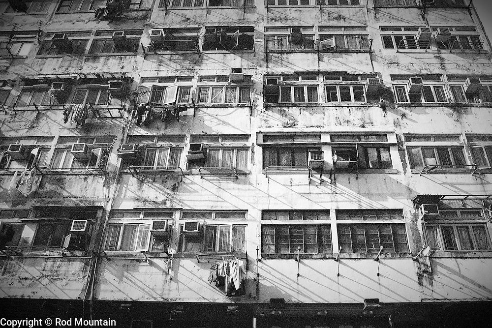 Hong Kong, China - 2009 - The exterior view of an older apartment building in Hong Kong where clothes hang to dry near the air conditioning units.<br />
