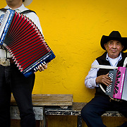 A pair of mariachis pass the time on Cesar Chavez Boulevard in East Los Angeles playing their music.